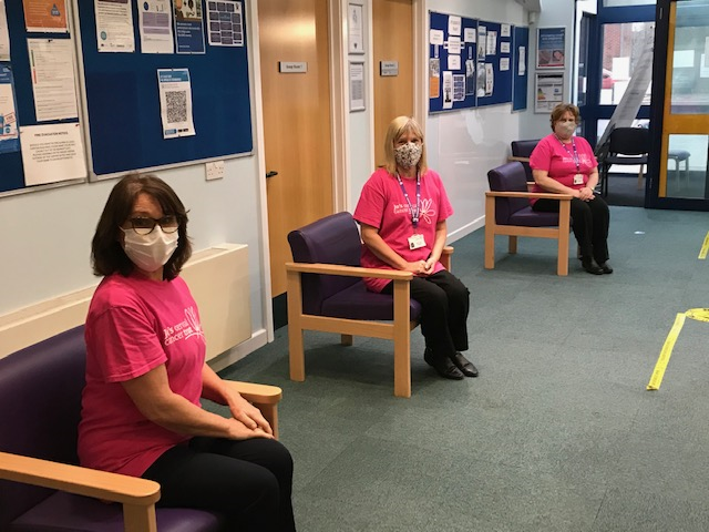 Reception team seated two meters apart wearing masks